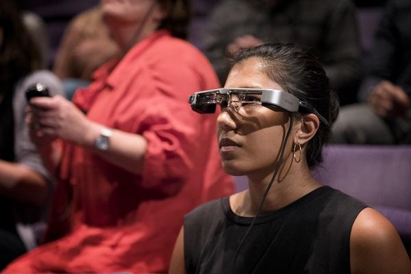 A woman wearing a set of captioning glasses