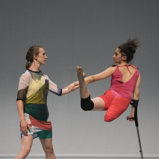 Two female dancers, one suspended in mid-air on a crutch