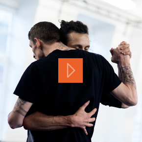 Two men dance whilst in a tender embrace
