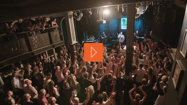 A crowd with their arms in the air at a music gig