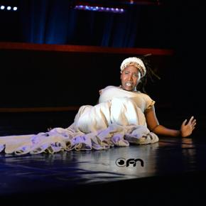 Black female performer lying on the ground