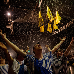 Group of men with arms aloft as glitter rains down on them