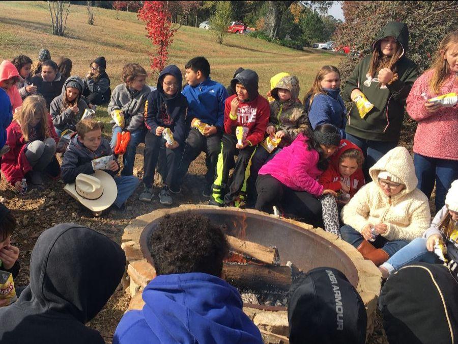 class gathered around a fire pit