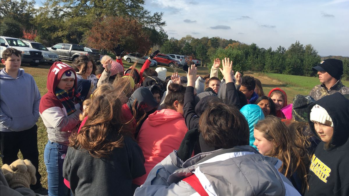 group of kids gathered around a speaker