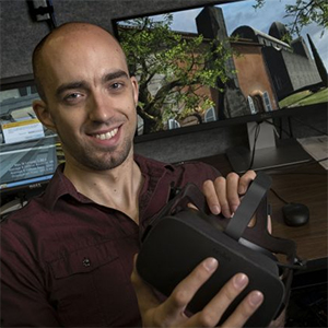Carl Schissler holds an Oculus VR headset in a lab in Sitterson Hall