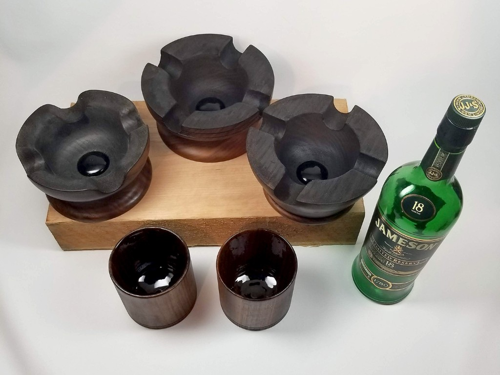 Three cigar ashtray's, two whiskey tumblers and a bottle of Jameson whiskey