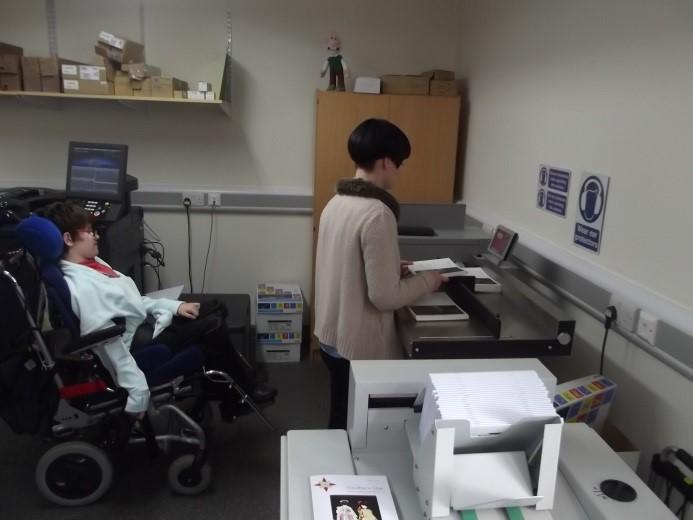 Student Yaffa working with Technician Megan to control the Morgana DigiFold Pro folding machine