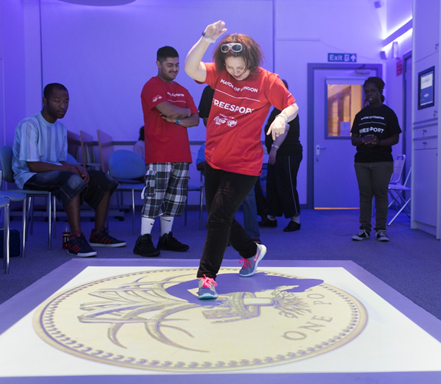 Student dancing on a projected image of a coin at the share community immersive space