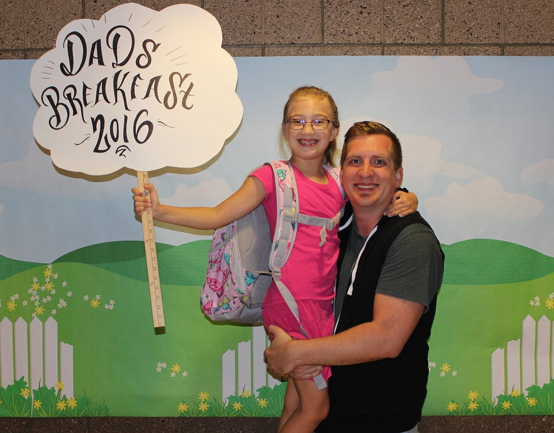 """A girl is held by her dad while she holds a """"Dad's Breakfast 2016"""" sign"""