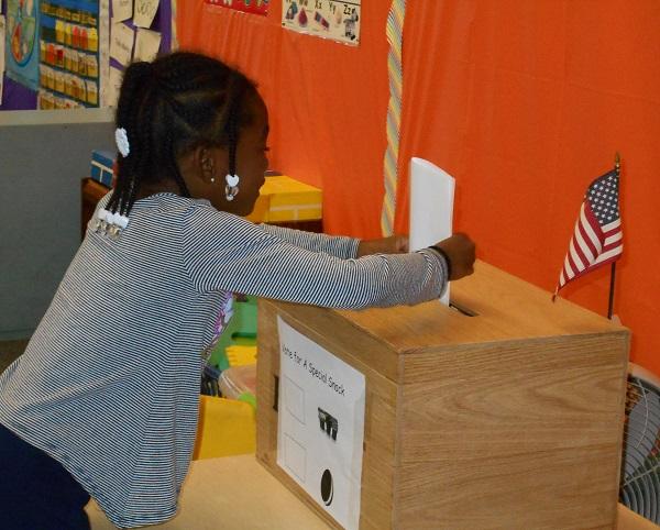 Young girls casts a ballot