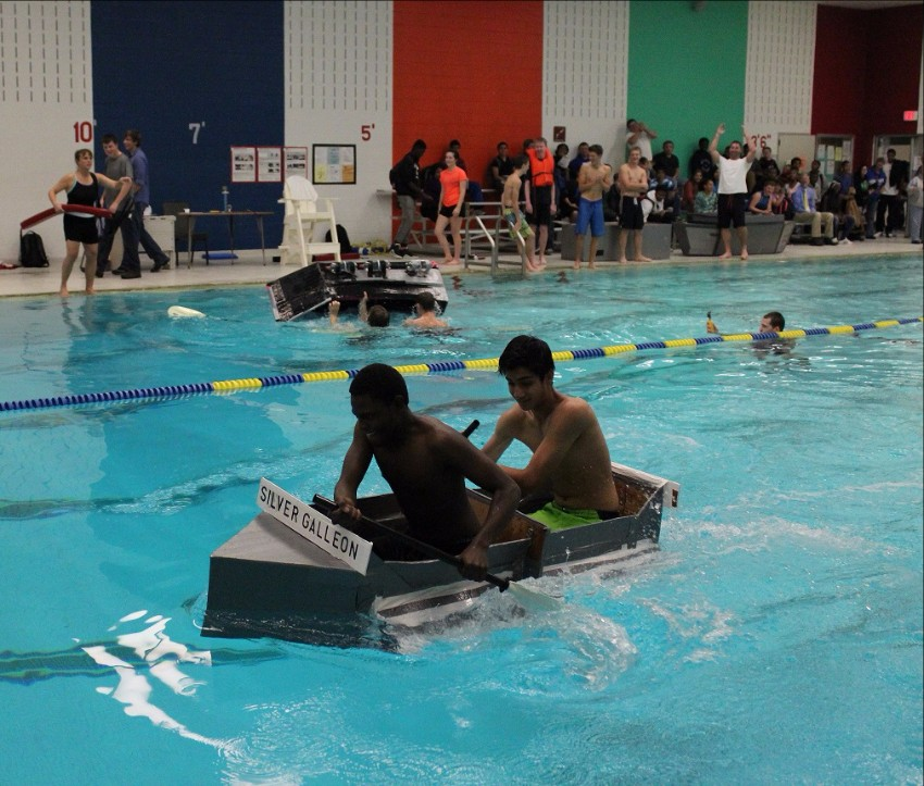 Boys paddle a cardboard boat in the high school swimming pool