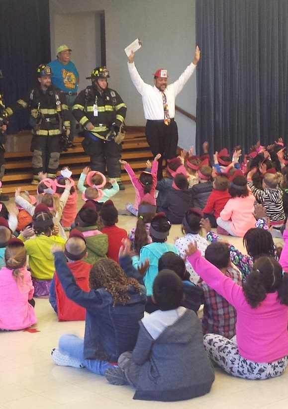 Kids quietly listen to the principal and firefighters