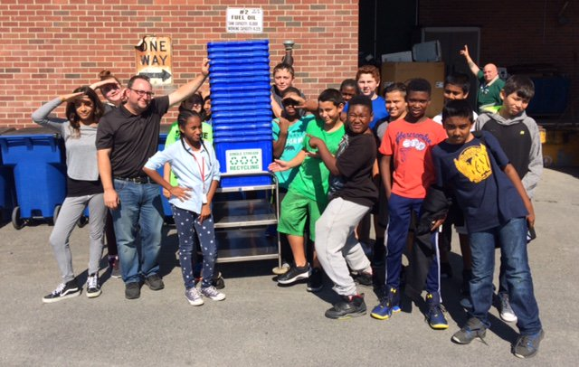 Students stand outside with a tower of recycling bins