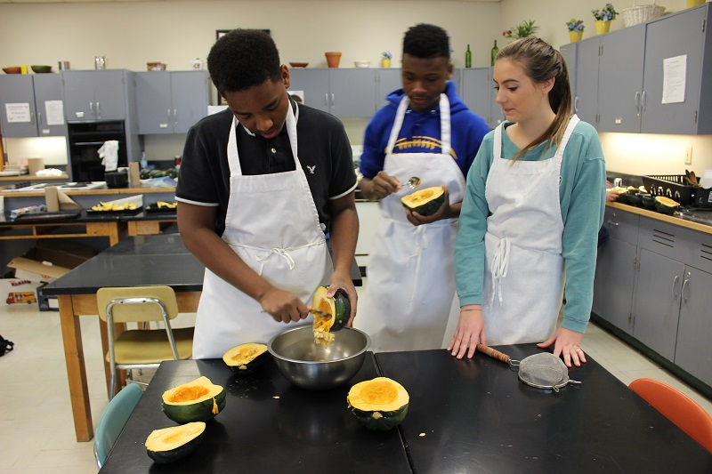 Students scoop seeds from acorn squashes