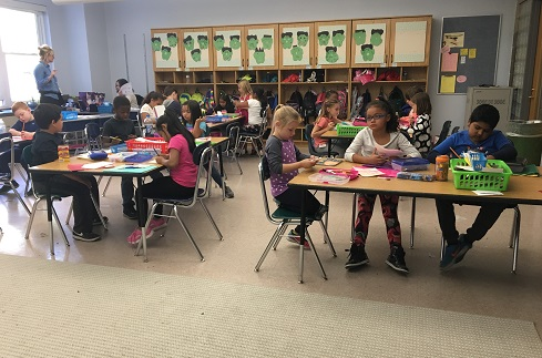 Second graders sit at new classroom tables