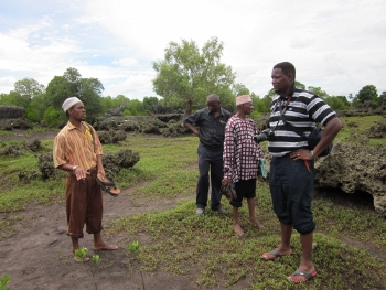 """Seacology's East Africa field representative Dishon Lionel Murage (right) explores a mangrove """"coral garden"""" -- limestone formations shaped by erosion."""