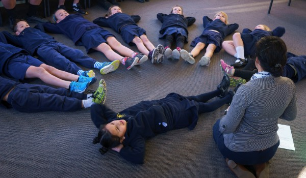 A group of school children lying on the floor doing an activity from the Sparklers toolkit.