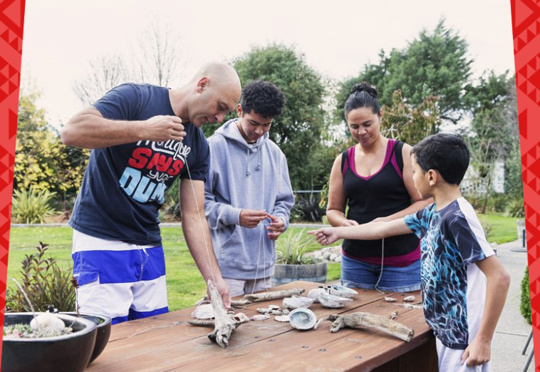 A Māori family doing a craft project together.