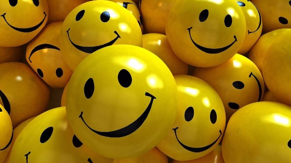Many yellow balls with smiley faces on them.