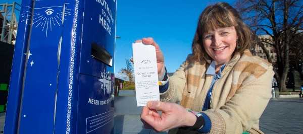 Gap Filler Co-Founder Coralie Winn with one of the special tickets issued by the new Open City meter in Cathedral Square.