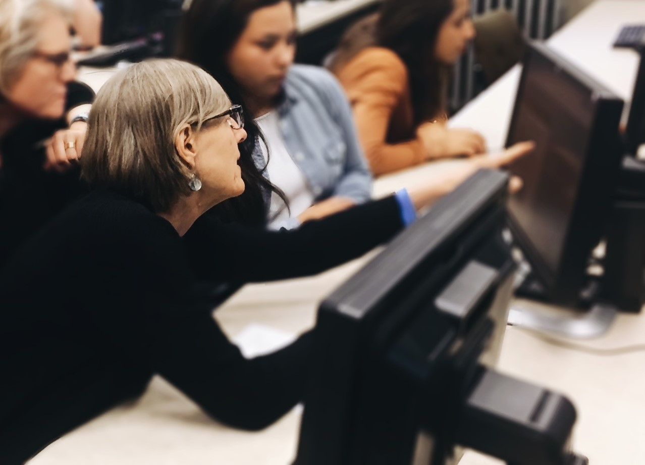 A woman points helpfully to another person's computer screen during a transcription session.