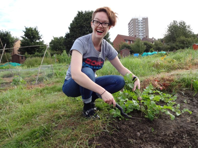 Image shows a white woman with short ginger hair and glasses wearing a jeans and tshirt. She is crouching down and digging up a radish from an allotment patch, and looks very happy.