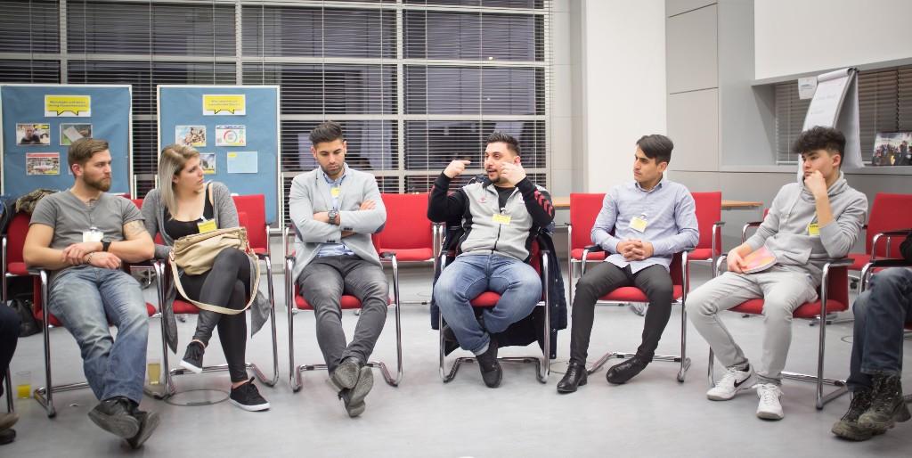 Teilnehmer sitzen im Sesselkreis