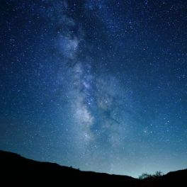 galaxy of stars stripping down a night sky, gradient from dark blue to light blue close to the horizon of low hills.