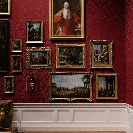 a European art gallery, many paintings in ornate gold frames on a luxurious red wall