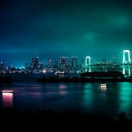 nighttime cityscape with neon lights reflected in water