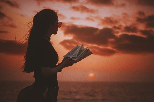 a person holding an open book looking into a red sunset over the ocean