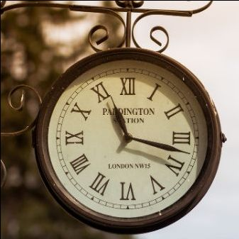 a train clock hanging from ornate metal, that says PADDINGTON STATION with the roman numerals for numbers. It is slightly before 11:20.