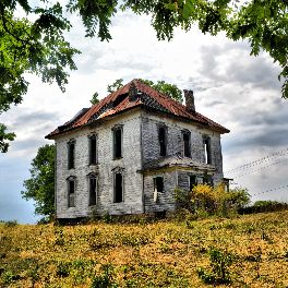 painting-photograph of a decaying and abandoned three-story house in the middle of a dead field.