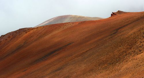 red desert sand going up a hill, another one in the distance; above, a grey cloudy sky.
