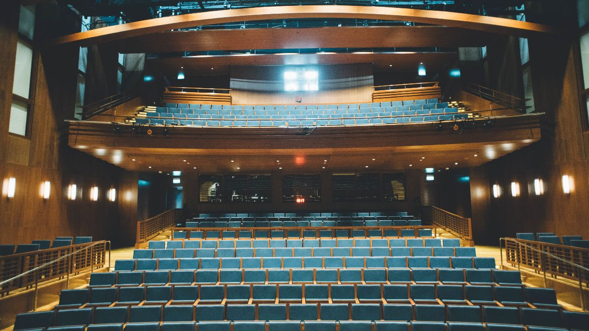 a photo of an empty auditorium from the position of the stage, with balcony seating