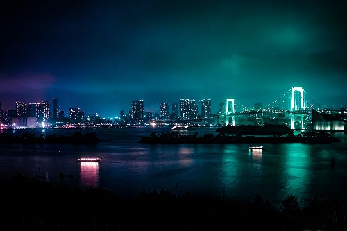 a cityscape from across a river, at night, lit up in bright neon colors reflected in the cloudy sky