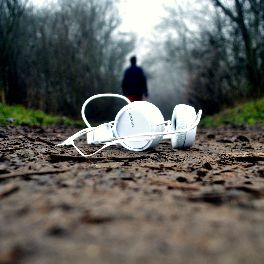 headphones on a dirt path with a shadow figure walking away