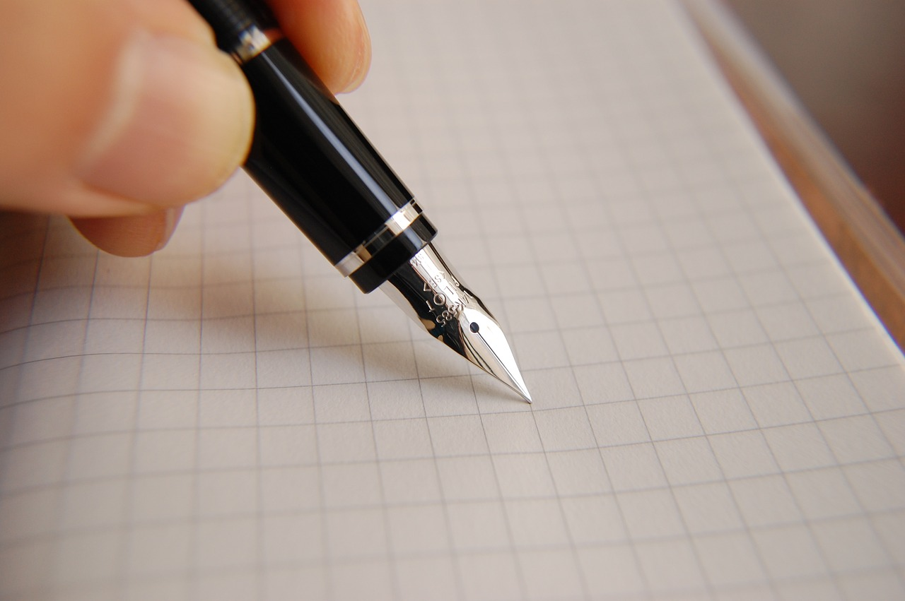 a hand holding a fountain pen against graph paper