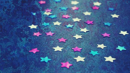 small metallic confetti stars - pink, blue, and gold - scattered across a marbled blue floor.
