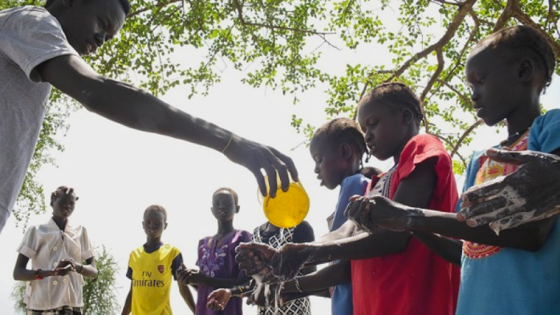Children in Kuach, South Sudan, learn how to wash their hands properly. USAID and its partners help communities learn about essential hygiene and health behavior to prevent diseases like cholera and diarrhea. Photo credit: UNICEF/Kate Holt.