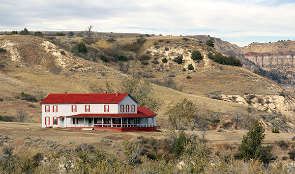 White building with red roof and shutters with buttes in the background