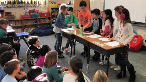 Students from one class demonstrate experiment for students from another class