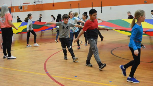 Two student groups working with large parachutes