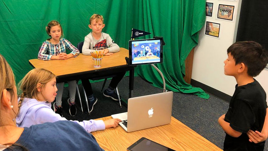 Second graders work on a classroom news broadcast
