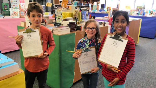 Students work on wish lists at Book Fair