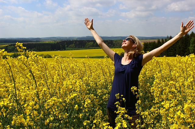 Woman Standing in field of yellow flowers, arms outstretched to heaven expressing happiness, gratitude for Nature