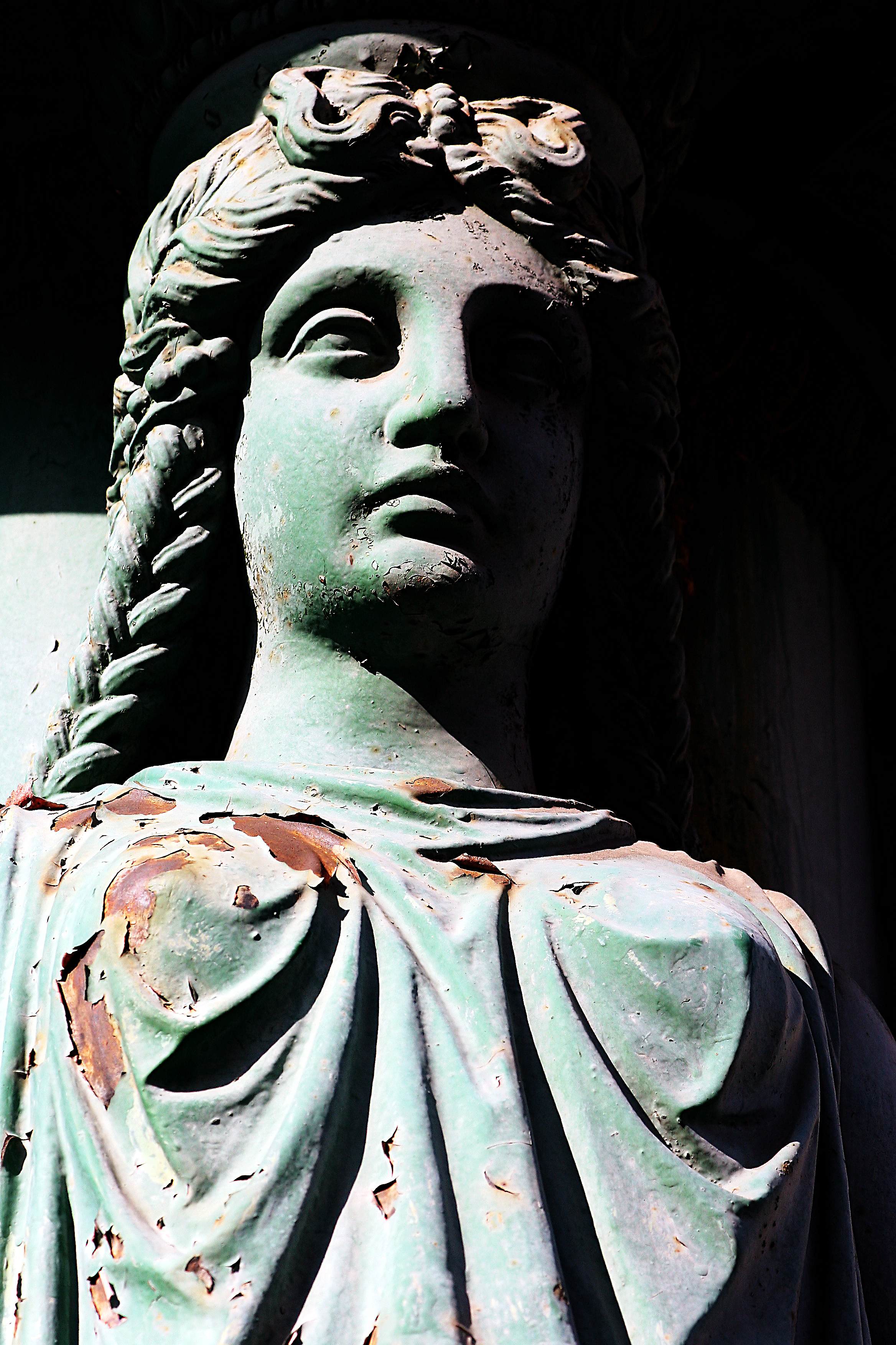 Medieval statue, female in robes with braided hair