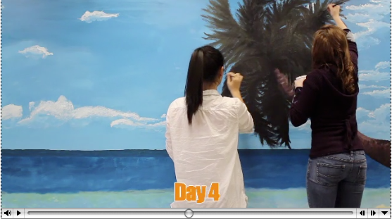 Students paint a mural of a beach, blue sky and palm tree on a wall.