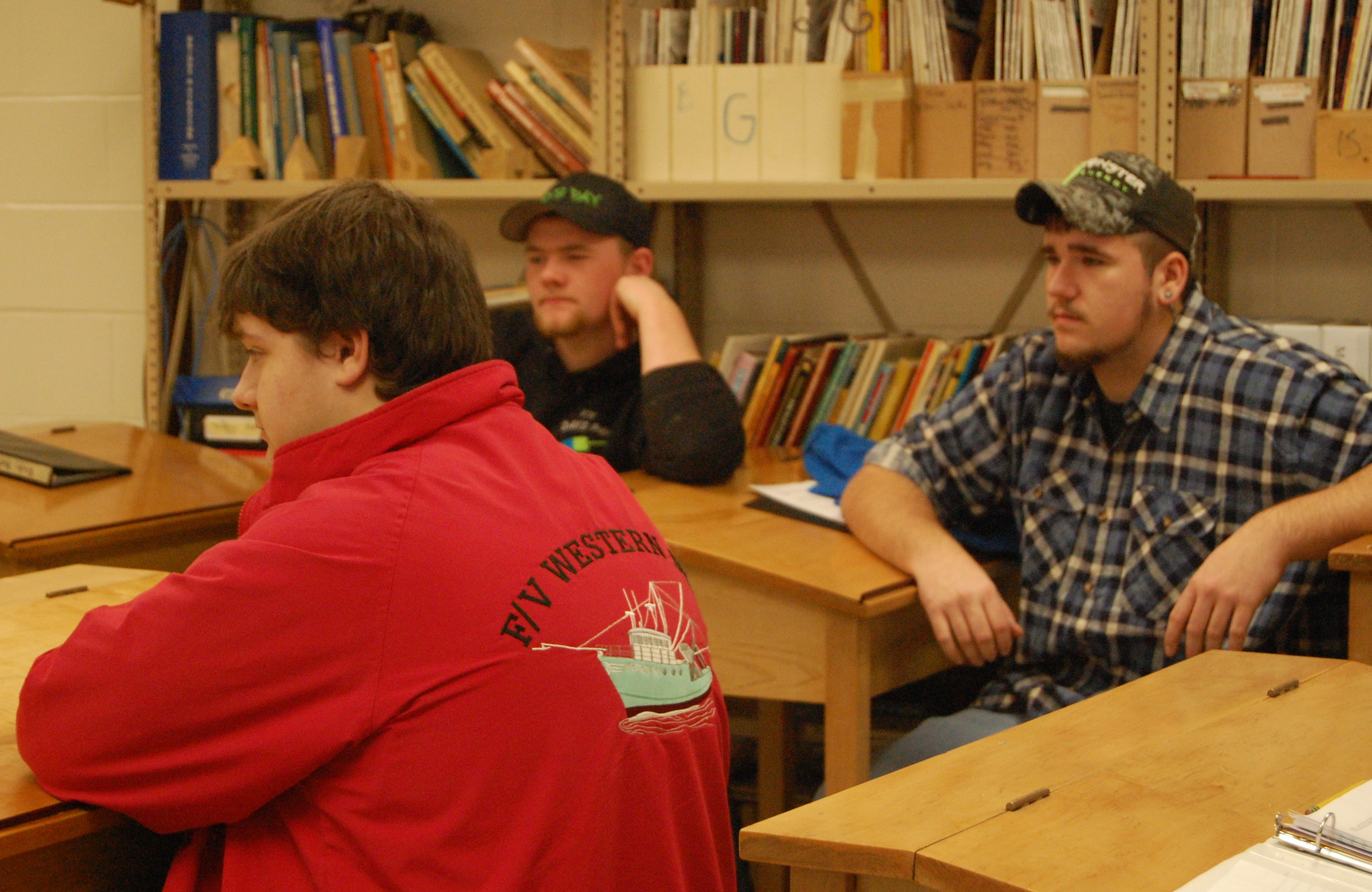 Students Lucas Eaton (black cap), Devon Olson (green cap) and Dan Fill explain their interest in DISHS' up-and-coming marine trades pathway to Commissioner Bowen.