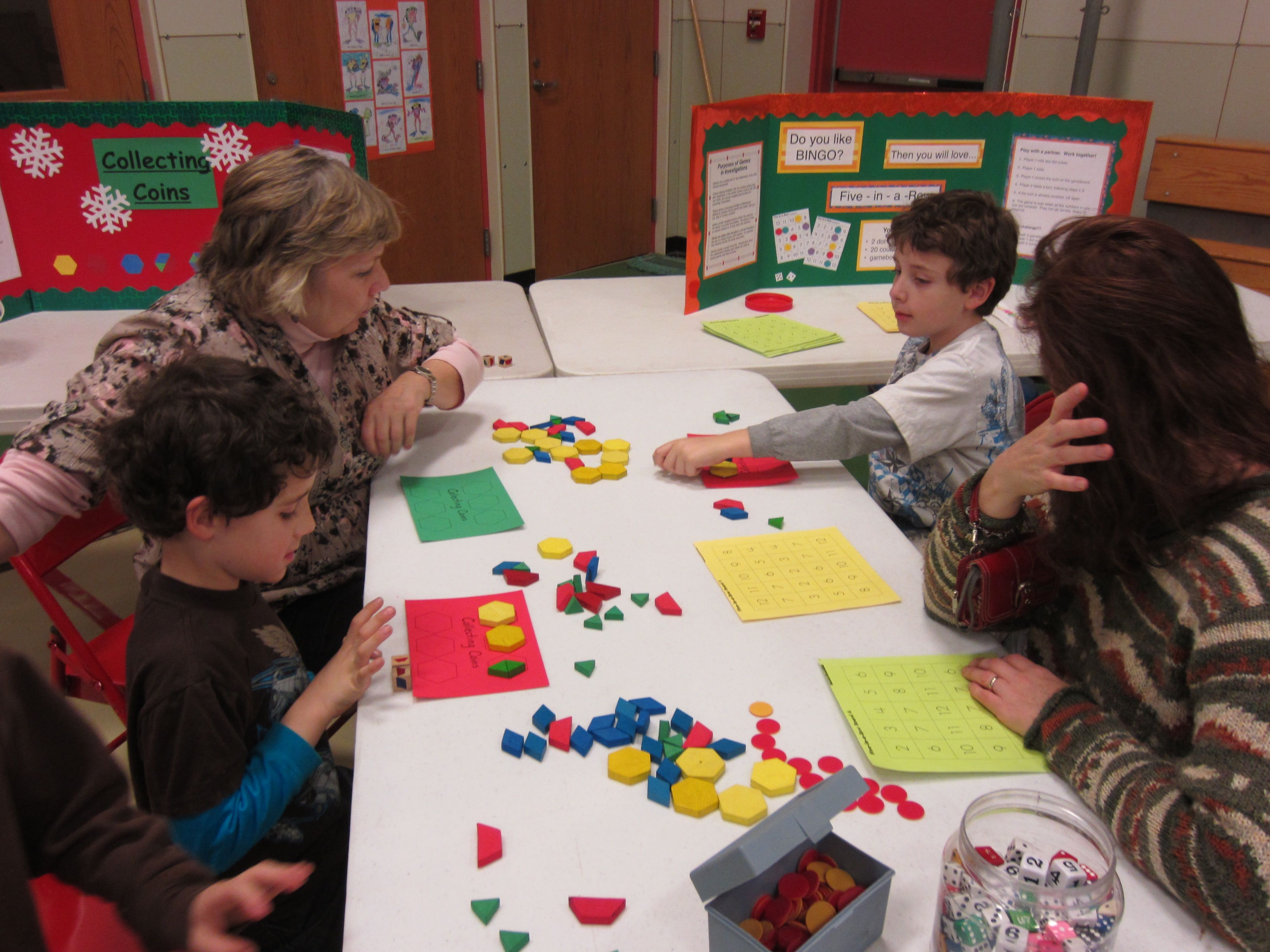 First grade teacher Laurie Malcolm (upper left) studies shapes with the Reiter family during Math Mania night at Laura E. Richards School.